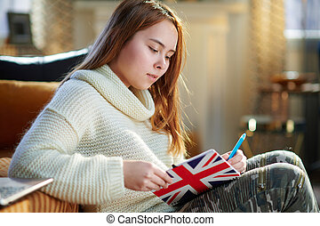 modern young woman writing in notebook colors of British flag