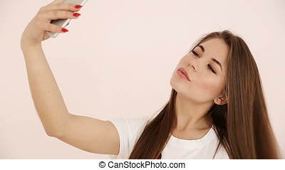 modern youth. beautiful long-haired European-looking girl with brown hair does selfie on a smartphone near a white wall
