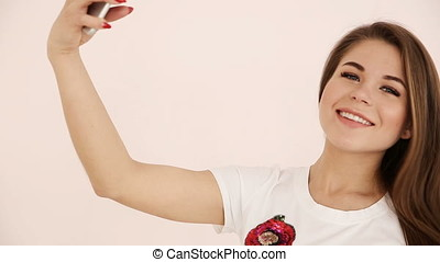 modern youth. beautiful long-haired girl of European appearance with brown hair expressively talking on a video communication smartphone near the white wall