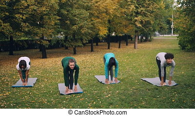Modern youth is doing yoga in city park learning from...