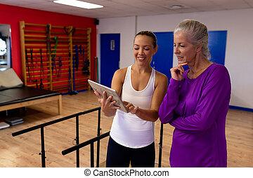 moderne, femme, discuter, centre, sports, femme, handicapé, personne agee, kinésithérapeute