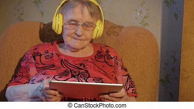 moderno, nonna, con, pc tavoletta, e, cuffie