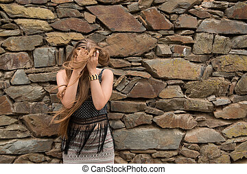 young woman on the background of the old stone wall