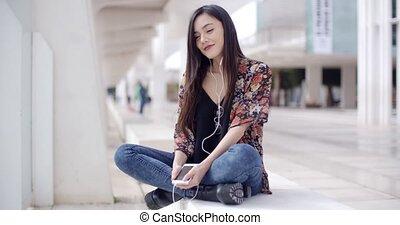 modieus, jonge vrouw , horende muziek, in, stad