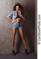 modisch, brünett, schöne frau, posierend, in, studio, tragen, kurz, und, jacke, jeans, anschauen, kamera.