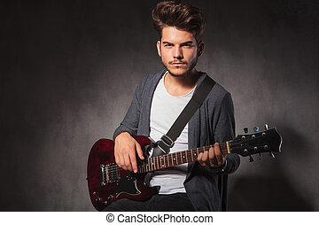 modisch, künstler, spielende gitarre, in, dunkel, studio, hintergrund