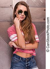 modny, girl., piękny, młoda kobieta, w, sunglasses, dzierżawa wręcza, na, podbródek, i, aparat fotograficzny przeglądnięcia, znowu, reputacja, przeciw, metal, tło