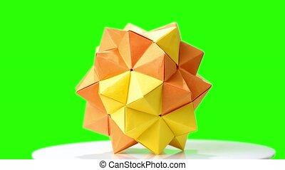 Modular origami flower on green screen. Yellow origami ball...