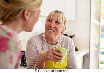 moeder en dochter, klesten, drinkende koffie, in, keuken