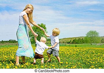 moeder en kinderen, spelend, en, dancing, buiten, in, bloemenweide
