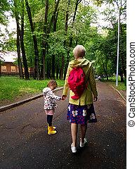 moeder, en, weinig; niet zo(veel), krullend, toddler, meisje, samen lopend, in, een, park, op, een, nat, zomer dag, na regen, aanzicht, van de rug