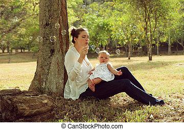 moeder het spelen, zeep, bobbles, met, weinig; niet zo(veel), baby dochter, in park
