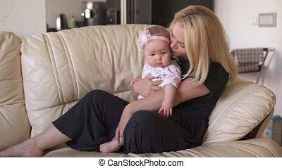 moeder, schattige, kussen, baby, haar, omhelzingen, sofa