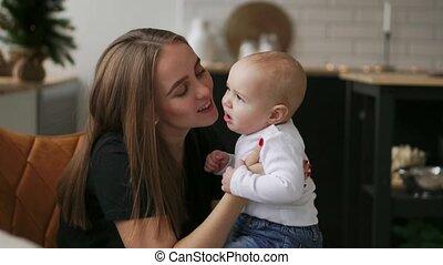 moederschap, vrolijke , vertragen, keuken, mooi, eva, moederschap, mother., kerstmis, mamma, omhelzingen, geliefd, moeder, liggen, stander, glimlachen, kussende , zijn, het kijken, motie, garlands, hugging., beeldmateriaal, baby, video, achtergrond, samen, kind, gezin, concept, bomen., witte