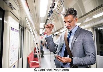 mogna, affärsman, med, smartphone, in, a, metro, train.