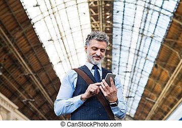 mogna, affärsman, med, smartphone, på, a, tåg, station.