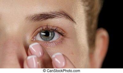 Moisturize skin around the eyes. Make up. Closeup -...