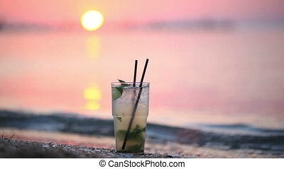 Close up of glass of mojito alcoholic cocktail standing in the sand on a tropical beach at sunset in the evening against a solar disk moving down