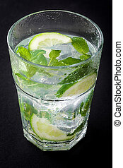 Mojito cocktail in glass on black stone