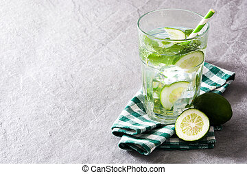 Mojito cocktail in glass on gray stone
