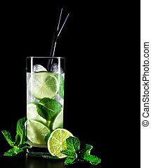 Mojito cocktail on black background with lime and mint