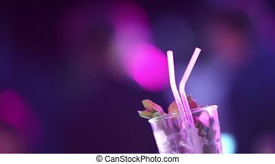 Mojito cocktail, party in the background, Stage lights on a...