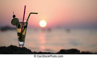 Mojito on the beach at sunset - Close-up shot of mojito...