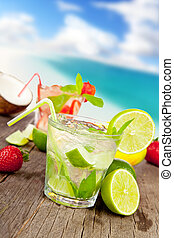 Mojito with pieces of fruit on wooden table. Blur beach on background