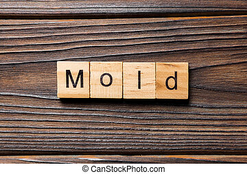 Mold word written on wood block. Mold text on table, concept