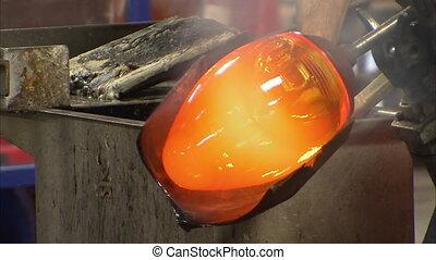 Molding a heated glass in an oval - A steady medium shot of...