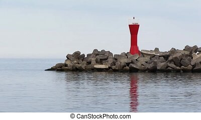 Mole at harbor with red navigational - Mole made of rocks at...