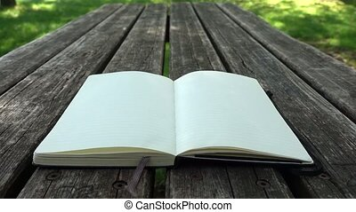 Moleskine notebook with striped pages on wooden table in a outdoor park. The pages turn in the wind.