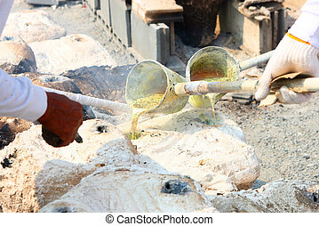 molten gold being poured from a foundry crucible