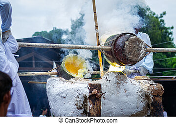Molten metal is poured into a sand mold aluminum casting and the Buddha temple is The ceremony of pouring Buddha image in Phitsanulok Thailand.