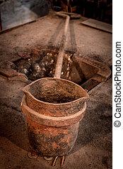 Molten metal pouring bucket in an iron smith shop