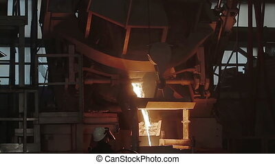 Molten metal pouring out of furnace. Liquid metal from blast...