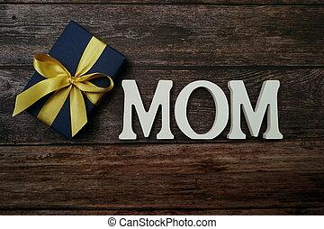 MOM alphabet on wooden background