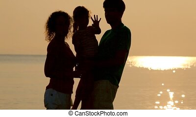 Mom an father hold daughter on hands, against the sunnysea backgraund