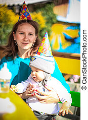 Mom and baby celebrate birthday in sunny day at outdoor