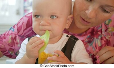 Mom and baby in a beautiful dress with butterfly eat in a cafe on the street. Kid eating a piece of cucumber salad mother