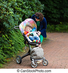 Mom and baby in a stroller - Young working mother and formal...