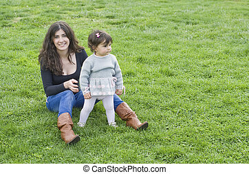 Mother and daughter in outdoors park on the grass.