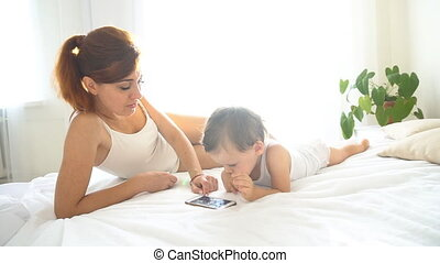 mom and baby look at smartphone in the bedroom