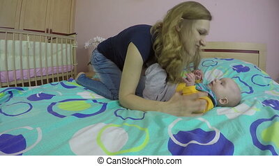 mom and baby play on bed