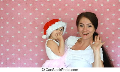 Mom and baby waving good bye. The concept of Christmas and New Year