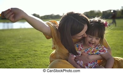 Mom and beautiful daughter laughing on meadow
