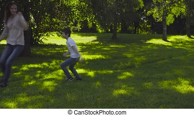 Mom and boy playing catch-up on the glade in the park at...
