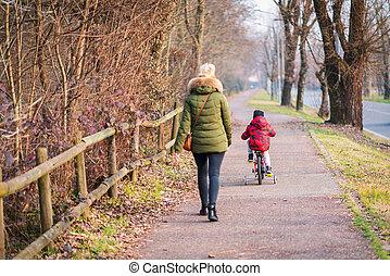 Mom and boy riding his bicycle on bike lane