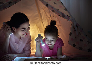 Family bedtime mom and child daughter are reading a book family bedtime mom and child daughter are reading a book with flashlights in tent pretty young mother and lovely girl having fun in children room sciox Gallery