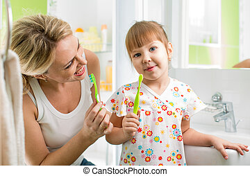 mom and child daughter brushing teeth in bathroom